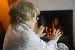 Older person warming hands at fire