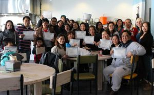 Course attendants hold up their certificates