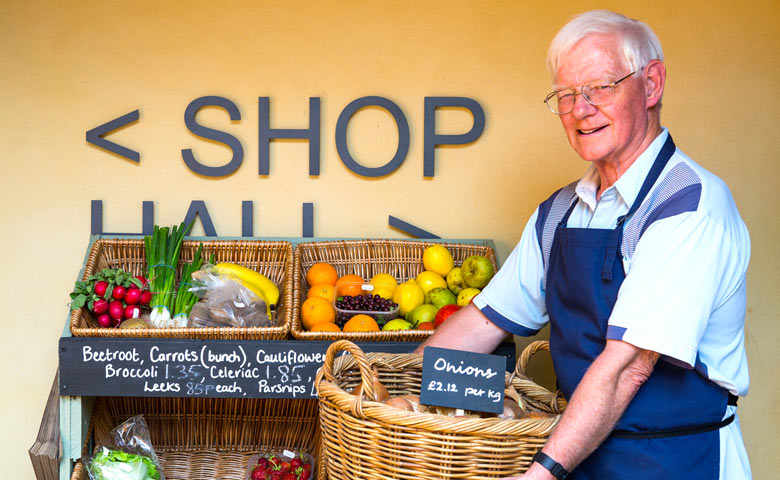Man with veg basket in community shop (Plunkett image)